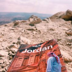 Lonely Planet Guide Book in mountains overlooking Wadi Rum desert Jordan