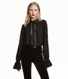 Black. Long-sleeved blouse in airy woven fabric with a collar. Concealed buttons at front, lace trim inserts at placket and along sleeves, and elasticized