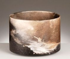 """Joanna Still     Open vessel: wheel-thrown, terra sigillata burnished to light sheen by stone, and smoke-fired unglazed.  Pieces """"are wrapped in various dry plant materials and buried in a kiln chamber filled with sawdust and wood shavings. This is lit from above and burns slowly down over several days creating a smoke filled environment which affects the pieces in unusual ways, leaving some areas deeply carbonized, others with atmospheric traces of plant imprints or smoke shadows""""."""