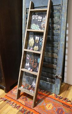 Store Jewelry on a small wooden ladder with a wire screen backing.  Shows things off.