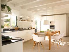 Cocina actual en blanco con office central y techo con vigas pintadas en blanco