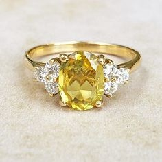 A modern update of a vintage style, this beautiful ring features a carat cushion-cut yellow sapphire accented by three round brilliant-cut diamonds on either side, set on an elegant yellow gold band. Yellow Engagement Rings, Vintage Engagement Rings, Oval Engagement, Yellow Sapphire Rings, Vintage Sapphire Rings, Pink Sapphire, Yellow Diamond Rings, Silver Jewellery Online, Thing 1