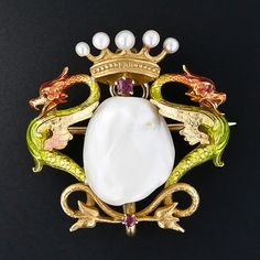 This gorgeous pin and/or pendant, circa 1900, shimmers with a sizable freshwater pearl (13.86 by 11.5 millimeters) closely guarded left and right by a pair of vigilant griffins (or dragons), and crowned - with a pearly crown! A superb and dramatic work of Art Nouveau. 1-inch both ways.