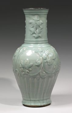A RARE MOLDED 'LONGQUAN' CELADON VASE  YUAN DYNASTY robustly potted, of large baluster shape with an ovoid body rising to a tall cylindrical neck, the shoulders crisply molded with scrolling lotus blossom and foliage borne on a continuous undulating stem, set between a neck decorated with three detached sprays of chrysanthemum blossoms, and carved overlapping upright leaves skirting the foot, covered overall in a rich unctuous bluish green glaze thinning to a pale gray