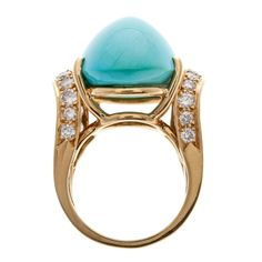 """18K yellow gold ring accented with 2.80 carats of diamonds. The cabochon Persian turquoise that caps the ring measures 26.6 x 16 millimeters."""
