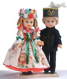 Strój Śląski z Górnikiem (mężatka)  strój kobiecy: spódnica gładka czerwona, zielona lub niebieska, suto marszczona, kwiecisty fartuch, biała bluzka z bufiastymi rękawami do łokcia, gorset zdobiony przy dekolcie układaną wstążką, na głowie wianek. strój męski: czarna marynarka zapinana na żółte, metalowe guziki, i proste długie spodnie, aksamitny wykładany kołnierz, czapka górnicza z pióropuszem koloru czarnego (górnik dołowy), białego (nadzór), czerwonego (członek orkiestry) lub zielonego…