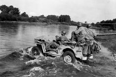 American GIs from the 45th Infantry Division's 157th Regiment ford the Moselle River in a Willy's Jeep, Fall 1944 near Igney, France.