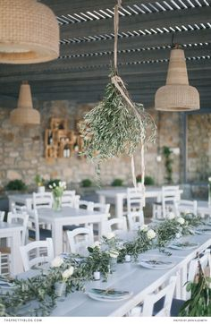 Olive tree branches make a great centerpiece. Low cost too if you know someone willing to let you prune theirs!