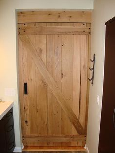 This beautiful rustic sliding barn door was built from reclaimed oak lumber. Built and installed by Gleman & Sons Orlando, Fla