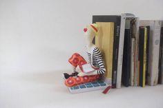 Escultura de palhaço em papel com estrutura em madeira que funciona como aparador de livros. Pode ser confeccionado com outros temas e em posições variadas. R$ 125,00
