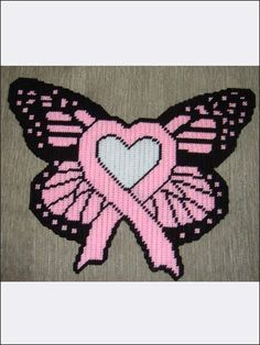 "Charitable Giving Patterns  ~~  Pink Ribbon & Pink  Heart Butterfly ~ Show your support with this beautiful pink ribbon butterfly. It is a great piece to keep for yourself or to give as a gift to someone you know fighting the fight.    Technique - Plastic Canvas   Size: 15 3/4"" x 12 3/4"". Made with medium (worsted) weight yarn and 7-count plastic canvas"