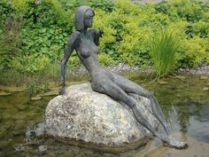 This is a statue of a sitting woman inside a small lake which is located in the Kurpark in Oberstdorf, Germany, Bayern.