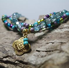 Czech glass Turquoise and Purples mix stretch bracelet with Teal firepolished faceted Preciosa glass and 17mm brass moorish charm and dangle.   Water Dance Stack Bracelet Set with Indie Charm by Angelof2, $24.00