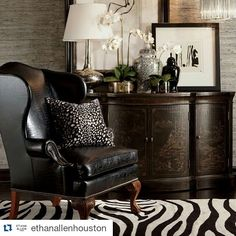 Love this entire grouping, leather chair, zebra rug, not sure what animal the pillow is, grass wall paper, accessories on chest and black & white art.