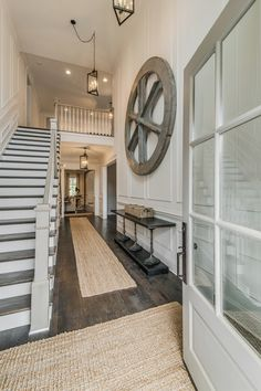 Open entry with hardwood floors, that wall trim and glass door. Grays and whites.