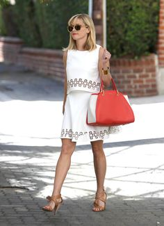 Reese slipped on her Monica Rose for Lovers + Friends two-piece number and then piled on the accessories. With two-tone Tory Burch sunglasses; her Maiyet tote; tan, tassel-embellished wedges; and a simple bangle, she's nailed the sophisticated prep look. The playful vibe her flouncy skirt's giving off is just the icing on the cake. Source: Getty / SMXRF/Star Max