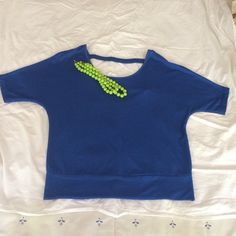 Top NWOT; Never worn; poly/rayon/spandex top accented with fabric crossbar on lower cut back. Ragland sleeves will contribute to comfort of this royal blue gem. Rebellious One Tops