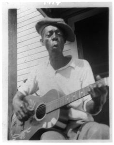 Bill Tatnall, a black folk musician, sitting on the porch playing his guitar in Frederica, Georgia. (1935) Photo by Alan Lomax