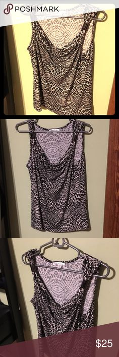 "Kenneth Cole Sleeveless Top Snakeskin type patterned top. Very beautiful with plunging neckline. Flowy stretchy material. Has 2 plastic clips on each side on the top to keep the ""straps"" in place. Colors are white, black, and a dark grayish color. Size Large.  Materials are 95% polyester, 5% spandex. Kenneth Cole Tops Blouses"