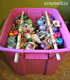 """Christmas storage: You'll know your ornaments are ready to be hung as soon as you pull them out next year if you loop the ribbon onto wooden rods in a plastic bin while they're in storage. This tip works well for """"shatter-proof"""" balls — but consider storing your favorite glass heirloom ornaments in individual containers."""