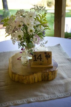 Wedding centerpiece. Burlap overlay, wood disk, jars for candles & flowers