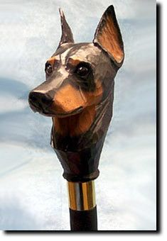 Doberman Dog Walking Stick. The Doberman Dog Walking Stick is a reproduction of an original woodcarving by Michael Park, a Master woodcarver, recognized worldwide for his detailed carvings and reproductions. Michael's passion and love for dogs are evident in his outstanding workmanship. Each walking stick is cast in resin and hand painted by master artists capturing a style of charm and warmth.