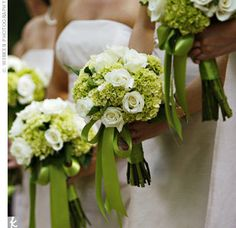 White roses, white ranunculis,  green hydrangea, purple calla lilies accented with green hypericum berries hand tied with dark purple ribbon with lime green cris cross