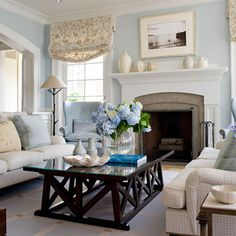 love it all! blue walls, cream couch, white accents, dark wood -- this could work in our new apt!