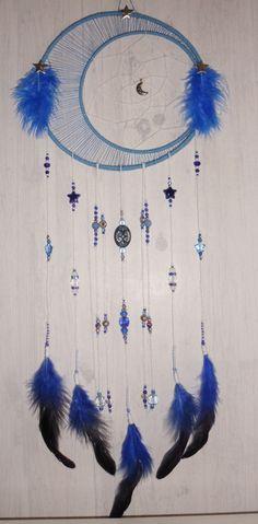 Superbe attrape-rêves, thème étoiles, à base de perles de qualité, de ficelle et de plumes.  La structure est en fil de fer, le tout recouvert de ficelle de coton bleu, et est décorée d'étoiles...