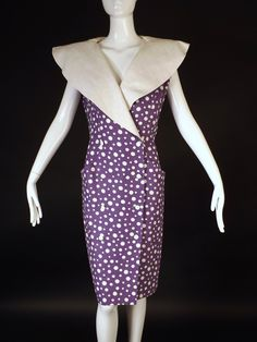 Fun springtime dress from the 1980s in a heavy linen of purple and white polka dots. The dart fitted dress has a wide collar and double breasted closures down the front. The dress is lined in linen. C