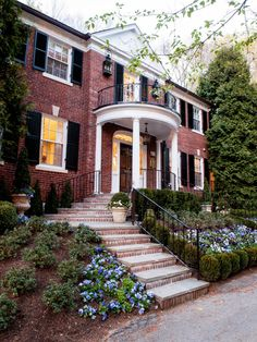 This brick Georgian Revival home has great curb appeal with brick stairs and lush landscaping.