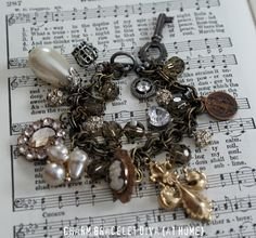 Vintage cameo, pearl, key, medal and fleur-de-lis charm bracelet