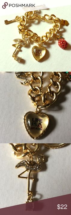 Juicy Couture Charm Bracelet Gold tone with 5attatched charms , a flamingo, a heart, a red fruit with gemstones, a key , and a logo charm. Has toggle clasp. Heart says life is a beach not new but not worn too small for me. Juicy Couture Jewelry Bracelets