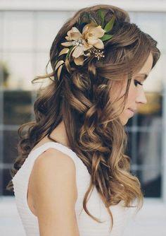 Une coiffure de mariage romantique avec des fleurs orangées