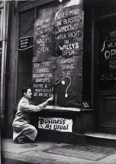 Wally's barber shop on St Martin Street has defiant signs after losing its windows during the London blitz. 1940