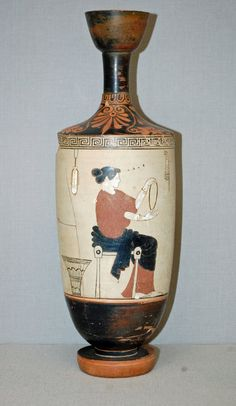 """Pottery: White-ground lekythos (oil-flask). """"On right hangs from the upper border a saccos."""" British Museum no. 1863,0728.312. Note sakkos' pattern of dots and patterned border, narrow tip, and cord at edge for securing the cap. Probably språng. Wool basket on floor."""