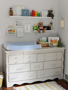love all of this - the long dresser used as changing table, light on wall, two different length shelves with frames on wall, the yellow IKEA rug