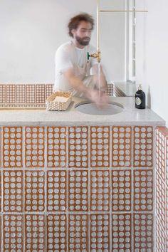 Casa de croissants, com fachada branca e janelas e portas em vidro, feita por dentro com blocos aparentes no piso, balcão e banco; pintura branca nas paredes; tubos de papelão no forro com iluminação embutida e pendentes cilíndricos dourados; bancada em granito com cuba redonda embutida, torneira dourada; eletrodomésticos para folhados, caixa. Na loja Mintchi Croissant, em Pinheiros. #loja #decoração #croissant #designdeinteriores #arquitetura #urbanismo #comercial #projetocomercial