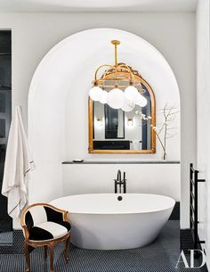 A Ralph Lauren Home light fixture illuminates the master bath's Victoria + Albert tub, which has Dornbracht fittings; the mirror and chair are antique, and the penny tile is by Waterworks.
