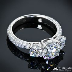 custom 3 Stone Pave Diamond Engagement Ring is set in platinum and holds 0.70ctw A CUT ABOVE® Hearts and Arrows Diamond Melee along the 3/4 eternity shank and baskets. This beauty features 3 A CUT ABOVE® Diamonds, the center being a 1.227ct and the side stones being a 0.33ct and 0.332ct.