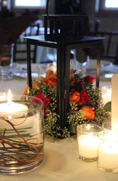 A beautiful Centerpiece using flowers inside of a lantern with votive candles and votive candles surrounding it for a wedding reception at The Goei Center.