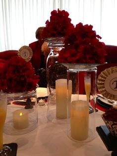 Easy centerpiece idea -- upside down cylinders/vases,  battery operated candles, topped with glass plates with blooms.  Impressive presentation.
