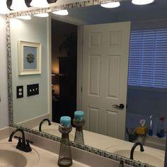 Use adhesive tiles to create frame around bathroom mirrors