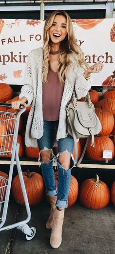 Gray cardigan over rose top and blue jeans.