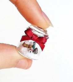 This beautiful miniature jar contains a little Christmas scene! This winter wonderland is composed by a snowman, a Christmas tree and a little cottage
