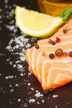 Raw salmon steak close up on black board with spices and lemon by Anastasy Yarmolovich #AnastasyYarmolovichFineArtPhotography  #ArtForHome #Food