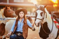 She - Beautiful womam sensuality elegance woman cowgirl on during sunset, riding a horse. Clothed blue jeans, brown leather jacket and hat. Has slim sport body. Portrait nature. People and animals. Equestrian. vintage style