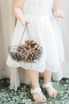 Have your flower girl carry pinecones for a rustic outdoor wedding! http://www.stylemepretty.com/arizona-weddings/greer/2015/09/14/rustic-romantic-arizona-summer-wedding-2/   Photography: Andrew Jade - http://andrewjadephoto.com/