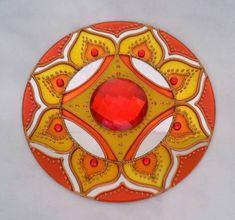 Mandala em CD reciclado de 12 cm de diâmetro, pintura vitral, decorado com tinta relevo dourada e pedrinhas em acrílico. Possui um gancho de metal para ser pendurada na parede. R$ 18,00