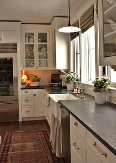 love this kitchen! soapstone counters, apron front sink with curtain below, wood floors with antique rug, bead board ceiling, glass doors